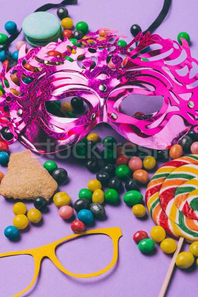 close up view of masquerade masks and candies isolated on purple Stock photo © LightFieldStudios
