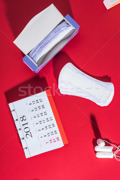 top view of tampons, daily liners and calendar on red Stock photo © LightFieldStudios