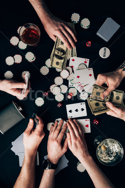 People playing poker by casino table with money and chips Stock photo © LightFieldStudios