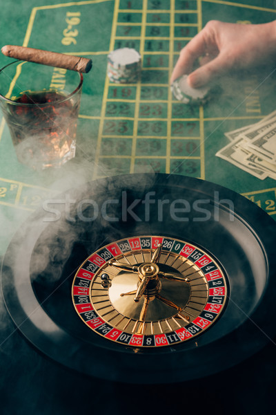Smoke over female hand placing a bet on table with roulette Stock photo © LightFieldStudios