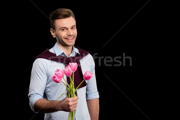 Handsome young man holding pink tulips and smiling at camera on black, international womens day conc Stock photo © LightFieldStudios