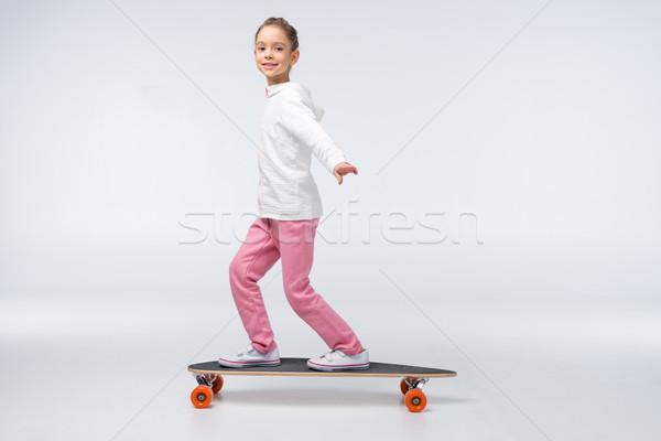 вид сбоку улыбаясь девушки верховая езда скейтборде белый Сток-фото © LightFieldStudios
