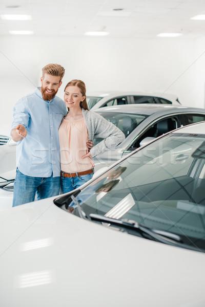 Happy couple choosing car in dealership salon, man pointing on car Stock photo © LightFieldStudios