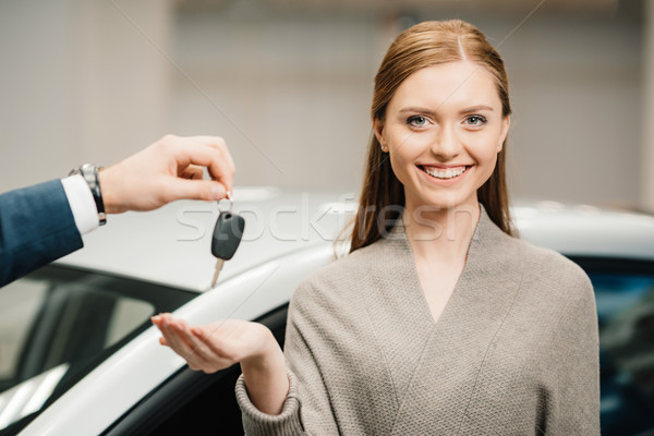 Dealer giving car key to beautiful young woman new owner Stock photo © LightFieldStudios