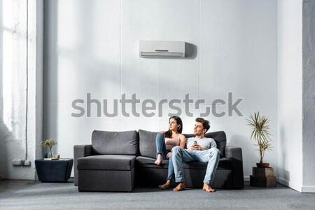 Woman kissing man sitting on chair Stock photo © LightFieldStudios
