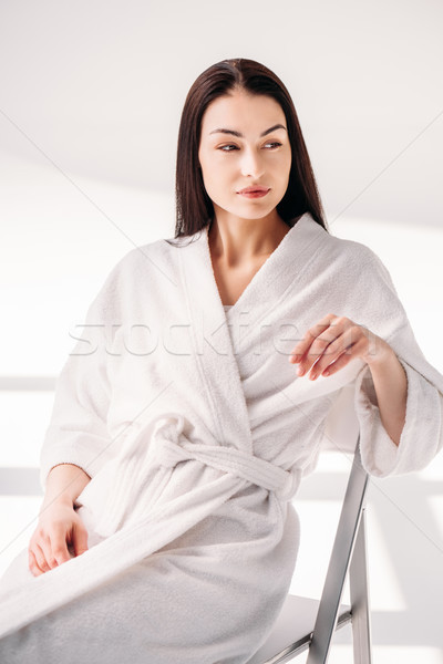young woman in bathrobe relaxing on chair Stock photo © LightFieldStudios