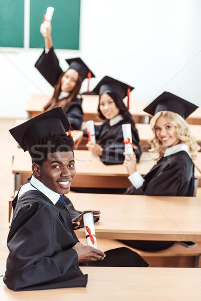 студентов окончания костюмы молодые сидят Сток-фото © LightFieldStudios