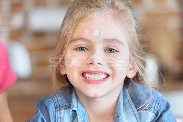 portrait of beautiful smiling girl with flour on face Stock photo © LightFieldStudios