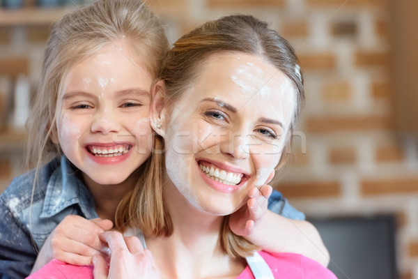 portrait of smiling mother and daughter in flour in kitchen Stock photo © LightFieldStudios
