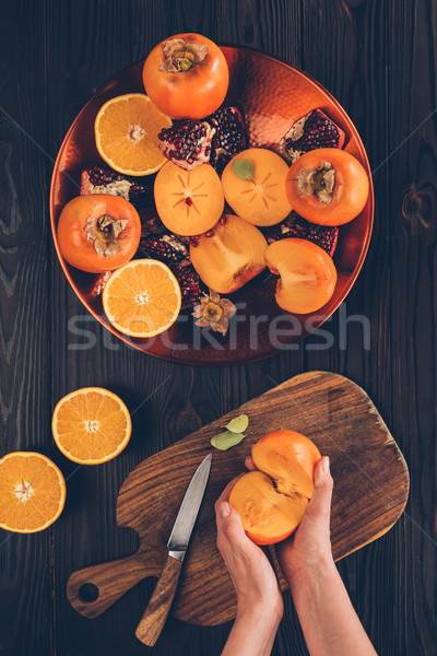 cropped image of woman holding cut persimmon pieces Stock photo © LightFieldStudios