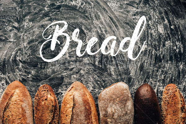 top view of arranged loafs of bread on dark tabletop with flour and bread lettering Stock photo © LightFieldStudios