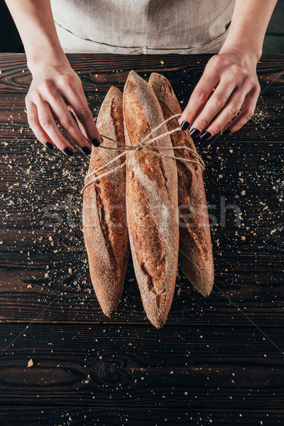 Partial view of woman tying rope around french baguettes on wooden surface Stock photo © LightFieldStudios