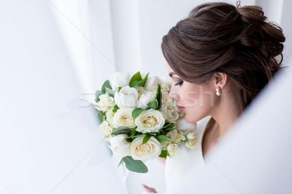 Stock photo: attractive brunette bride sniffing wedding bouquet