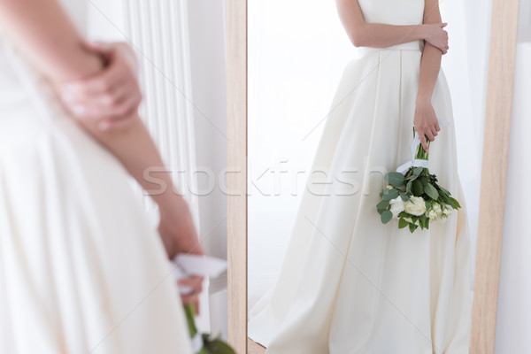 cropped view of bride in traditional dress with wedding bouquet looking at her reflection in mirror Stock photo © LightFieldStudios