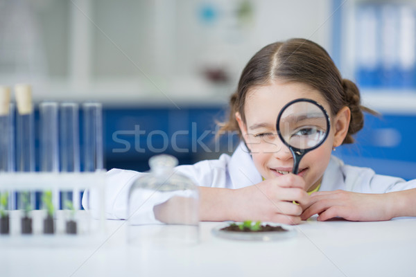 Smiling girl scientist holding magnifying glass and looking at camera Stock photo © LightFieldStudios
