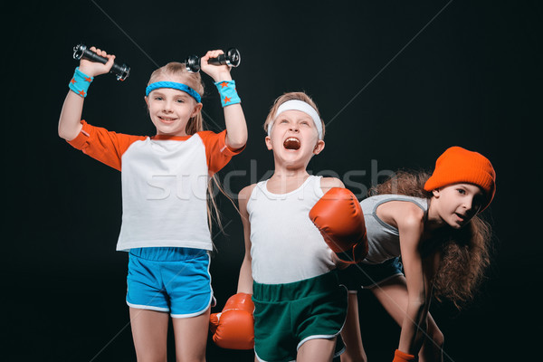 Three active kids in sportswear posing with sport equipment isolated on black Stock photo © LightFieldStudios