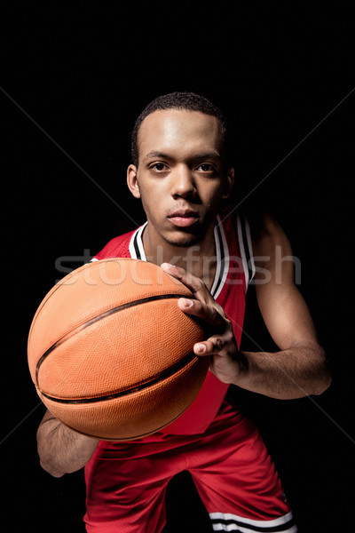 Young athletic man in uniform playing basketball on black  Stock photo © LightFieldStudios