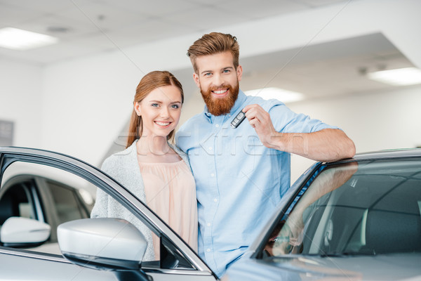 Stock photo: Happy couple holding car key and standing at car in dealership salon
