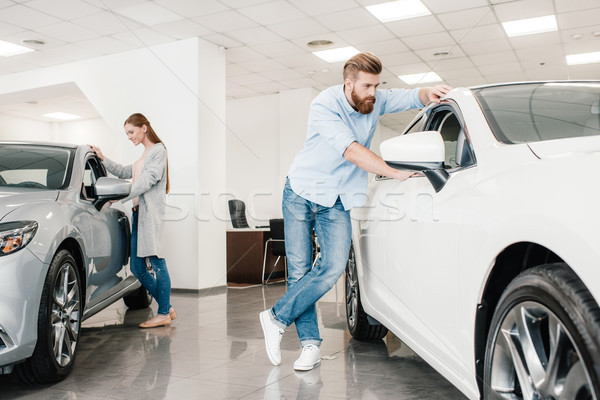Couple choosing car, man and woman looking on various cars in dealership salon    Stock photo © LightFieldStudios