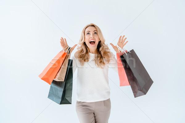 Meglepődött szőke nő tart bevásárlótáskák felfelé néz szürke Stock fotó © LightFieldStudios