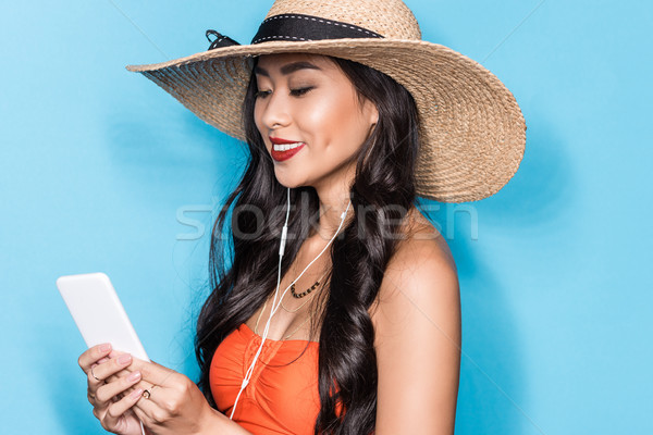 Woman in beach attire listening to music Stock photo © LightFieldStudios