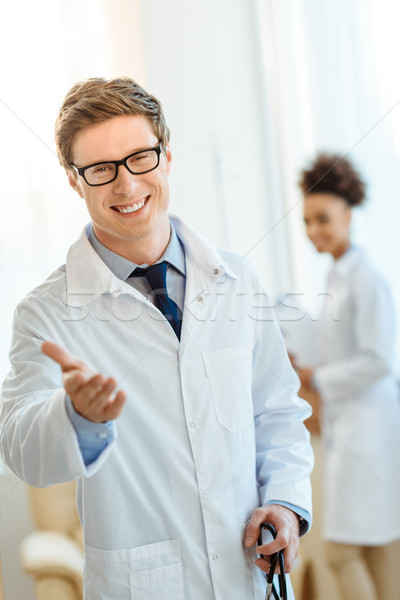 Smiling doctor holding out hand Stock photo © LightFieldStudios