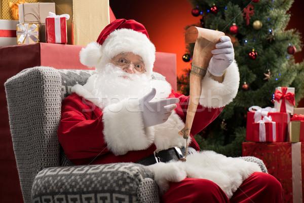 Santa Claus with wishlist in hands Stock photo © LightFieldStudios