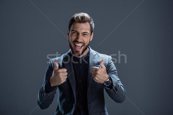 Man in suit showing thumbs up Stock photo © LightFieldStudios