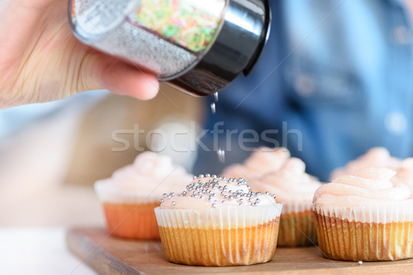 close up view of woman decorating cupcakes with confetti Stock photo © LightFieldStudios