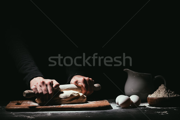 cropped shot of person preparing dough with rolling pin on black Stock photo © LightFieldStudios