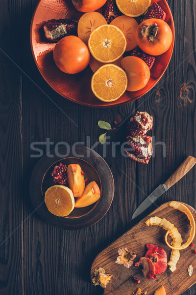 elevated view of persimmons with oranges and pomegranates on plates Stock photo © LightFieldStudios