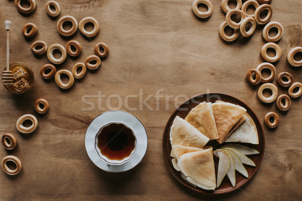 top view of tasty homemade pancakes with cup of tea, bagels and honey on wooden table Stock photo © LightFieldStudios