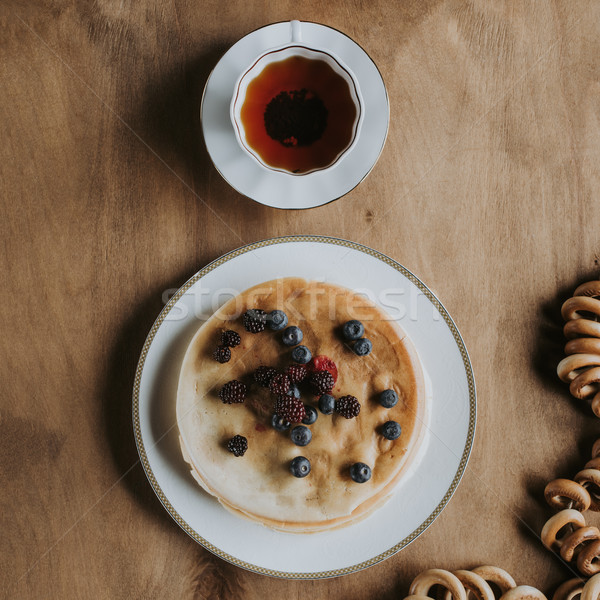 top view of delicious pancakes with berries, cup of tea and bagels on wooden table   Stock photo © LightFieldStudios