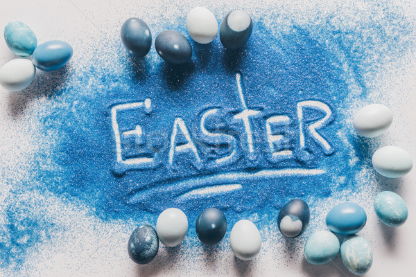 elevated view of easter sign made of blue sand with painted eggs on white Stock photo © LightFieldStudios