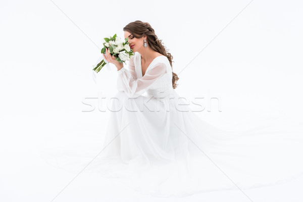 happy bride in traditional dress sniffing wedding bouquet, isolated on white Stock photo © LightFieldStudios