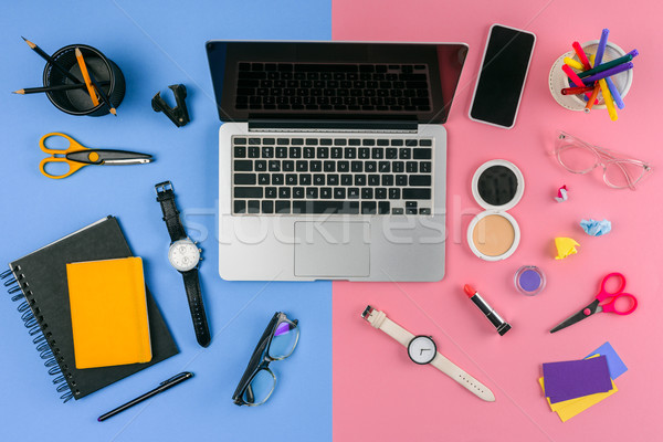 top view of laptop, smartphone and cosmetics with office supplies divided at male and female workpla Stock photo © LightFieldStudios