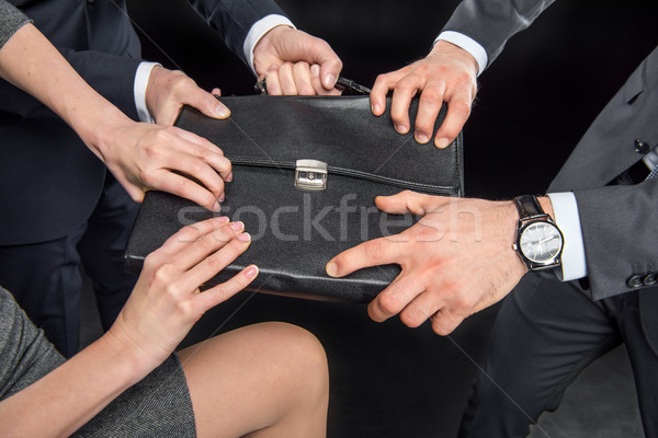 Businesspeople fighting for briefcase Stock photo © LightFieldStudios