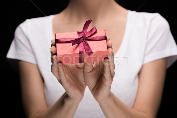 partial view woman showing gift in hands on black, international womens day concept Stock photo © LightFieldStudios
