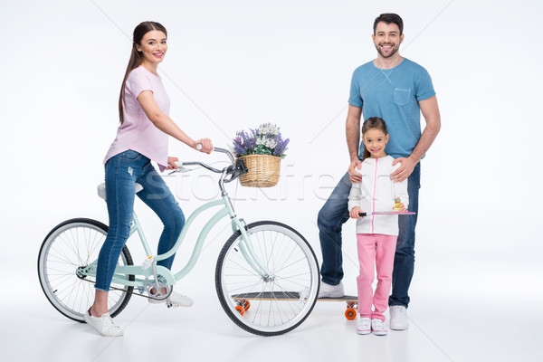 smiling family with skateboard, bicycle and badminton racket on white Stock photo © LightFieldStudios