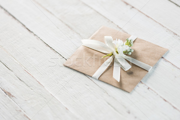 envelope with flower and ribbon on white wooden tabletop, invitation card wedding concept Stock photo © LightFieldStudios