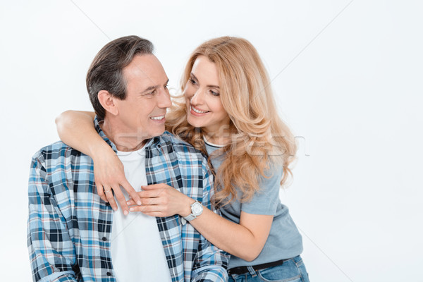 Front view of man and blonde woman embracing and smiling on white Stock photo © LightFieldStudios