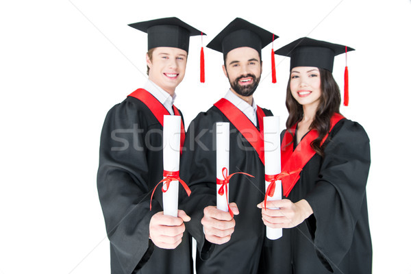 Happy students in graduation caps holding diplomas and smiling at camera  Stock photo © LightFieldStudios