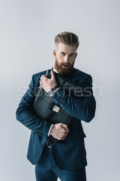 Stock photo: Handsome stylish businessman hugging briefcase and looking at camera