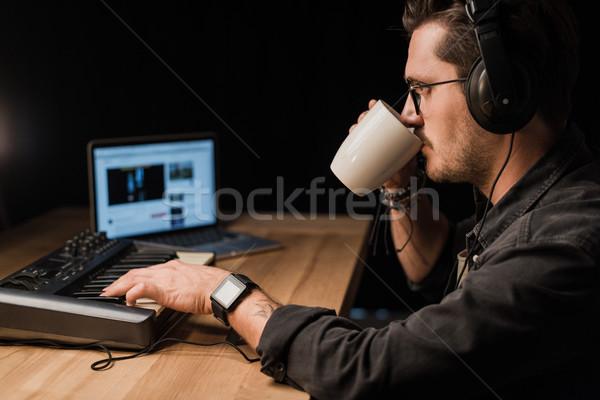 Zeneszerző fiatal zenész dolgozik billentyűzet sötét Stock fotó © LightFieldStudios