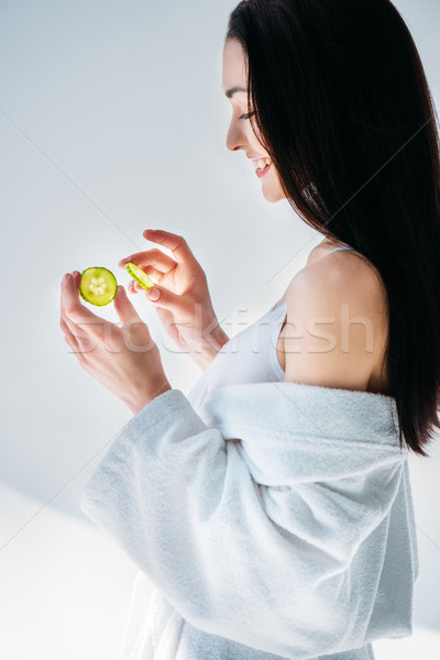 woman in bathrobe holding slices of cucumber Stock photo © LightFieldStudios