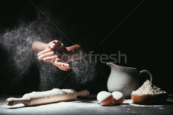 cropped shot of chef clapping ahnds with flour before making dough on black Stock photo © LightFieldStudios