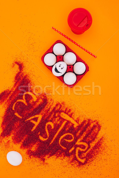 top view of easter sign made of red sand with chicken eggs with smiley on orange Stock photo © LightFieldStudios