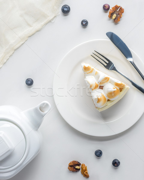 top view of appetizing piece of cake with meringue and teapot on white table Stock photo © LightFieldStudios