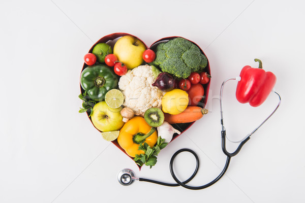 vegetables and fruits laying in heart shaped dish near pepper with stethoscope isolated on white bac Stock photo © LightFieldStudios