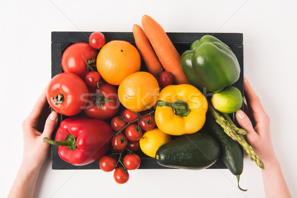 Hands holding vegetables and fruits in dark wooden box isolated on white background Stock photo © LightFieldStudios